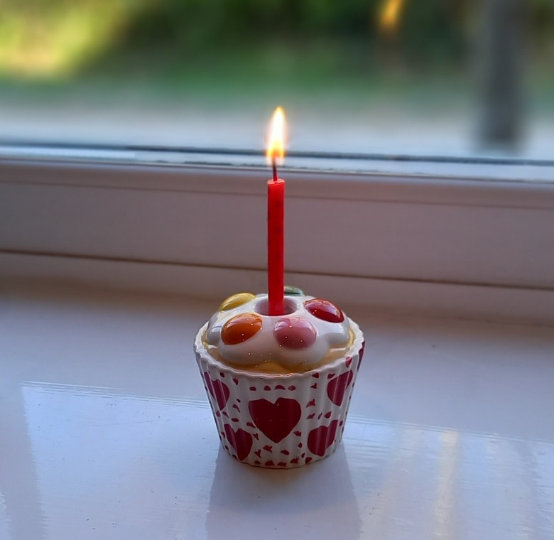 Ceramic candle holder shaped like a cup cake with a lit candle in the centre