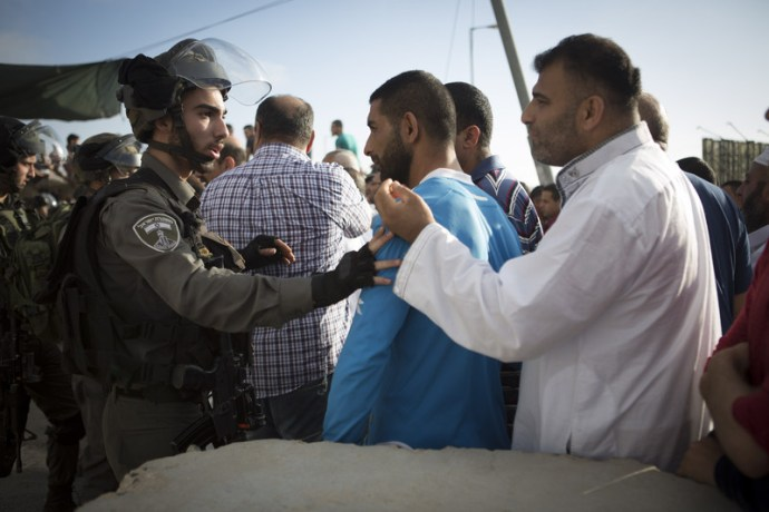 Israeli border police push Palestinian men as they try to cross through the Qalandiya checkpoint, between the cities of Jerusalem and Ramallah in the occupied West Bank, on 11 July. (Oren Ziv / ActiveStills)