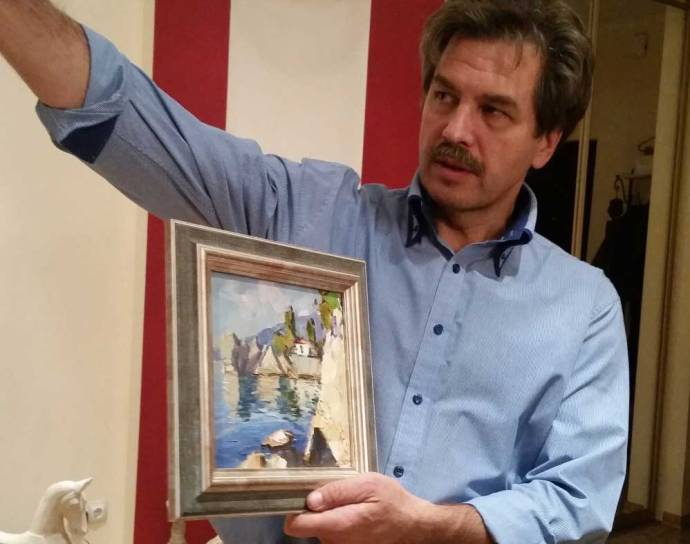 Nikolay in his St. Petersburg home with a painting of Chekhov's dacha in Ukraine