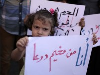 """I am from Deraa camp"" reads a sign held by a girl during a demonstration outside UNRWA's Gaza City headquarters in October 2013./ Ashraf Amra APA images"