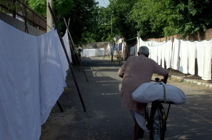 An old washerman leaves on his cycle to deliver the clothes.