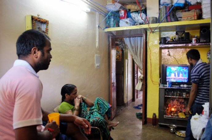 After a long day of work, Ashwani watches television with his mother.