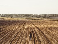 Young woman standing on the empty plowed field and looking away at the view