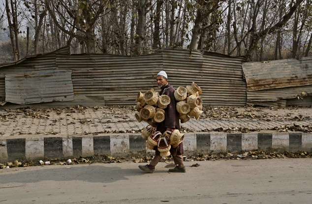 An elderly Kashmiri vendor sells Kangris or fire pots, on a cold morning in Srinagar, India, Monday, Nov. 24, 2014. Kangri is an age old device for keeping warm, consisting of a decoratively woven yellow wicker case housing an earthen pot for burning charcoal. (AP Photo/Mukhtar Khan)