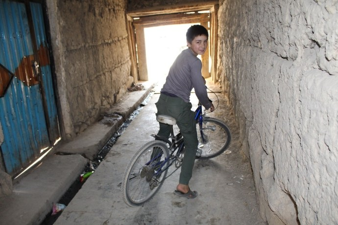 Inaam on his bicycle, near his house and the scene of a suicide bomb attack