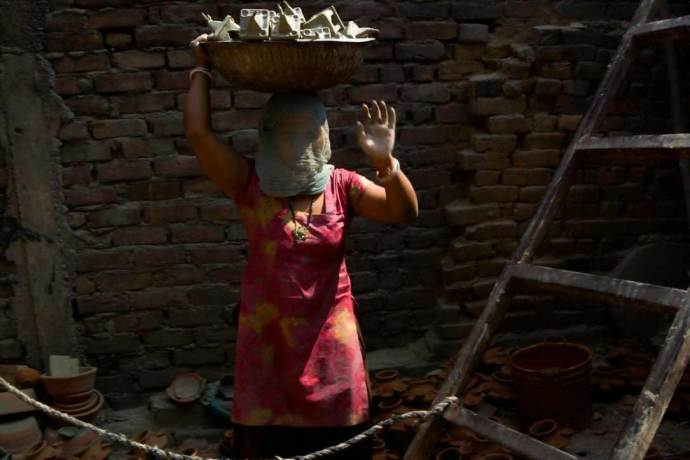 Woman climbing the ladder to and fro, lifting pottery wares.