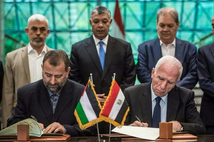 Hamas's new deputy leader Salah al-Aruri (seated L) and Fatah's Azzam al-Ahmad (seated R) sign a reconciliation deal in Cairo on October 12, 2017, as the two rival Palestinian movements ended their decade-long split following negotiations overseen by Egypt. Under the agreement, the West Bank-based Palestinian Authority is to resume full control of the Hamas-controlled Gaza Strip by December 1, according to a statement from Egypt's government. . Photo by STR