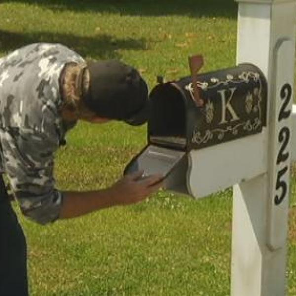 Man looking inside of mailbox