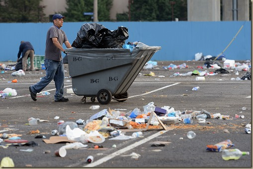 Bob Donaldson / Post-Gazette. 20140622. Bryan Concert Cleanup. Standalone. Local. Workers do an early-morning cleanup at the Carnegie Science Center parking lot at North Shore and Casino Drs. across the street from Heinz Field following Saturday night's Luke Bryan concert. Writer: Standalone. Story Slug: unknown