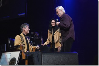 NASHVILLE, TN - FEBRUARY 08:  Kenny Rogers (right) greets Randy Travis (left) and Mary Davis (center) during 1 Night. 1 Place. 1 Time: A Heroes & Friends Tribute to Randy Travis at Bridgestone Arena on February 8, 2017 in Nashville, Tennessee.  (Photo by Rick Diamond/Getty Images for Outback Concerts)