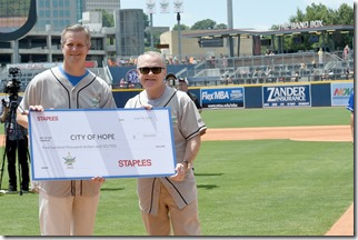 NASHVILLE, TN - JUNE 10: Chairman and CEO of Staples Ron Sargent (R) presents President and CEO of City of Hope Robert Stone with a check at the 27th Annual City of Hope Celebrity Softball Game at First Tennessee Park on June 10, 2017 in Nashville, Tennesse  (Photo by Rick Diamond/Getty Images for City Of Hope)