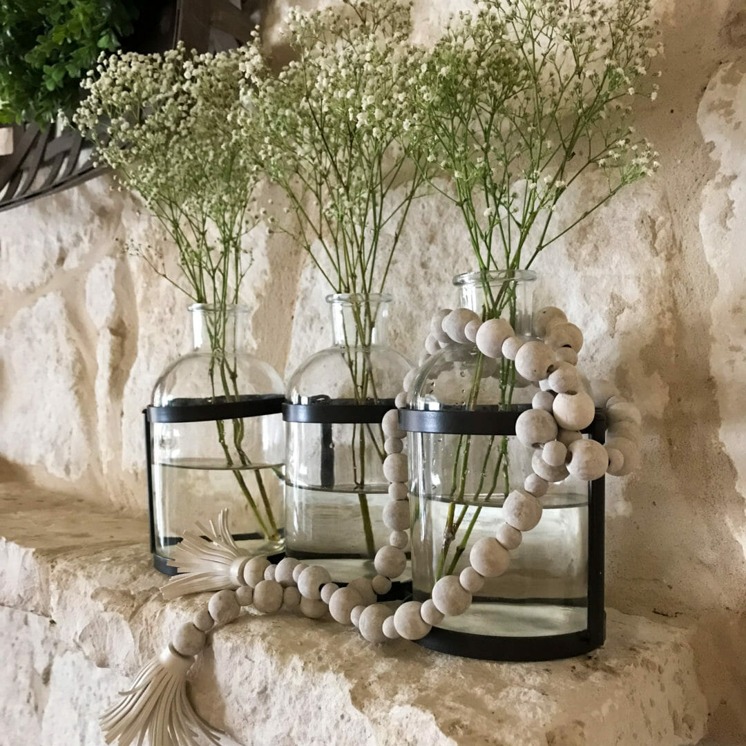 Glas vases with wood beads and baby's breath for a spring mantel pick-me-up. CountyRoad407.com