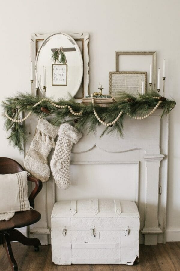 white mantel with frames, mirrors, greens and beads