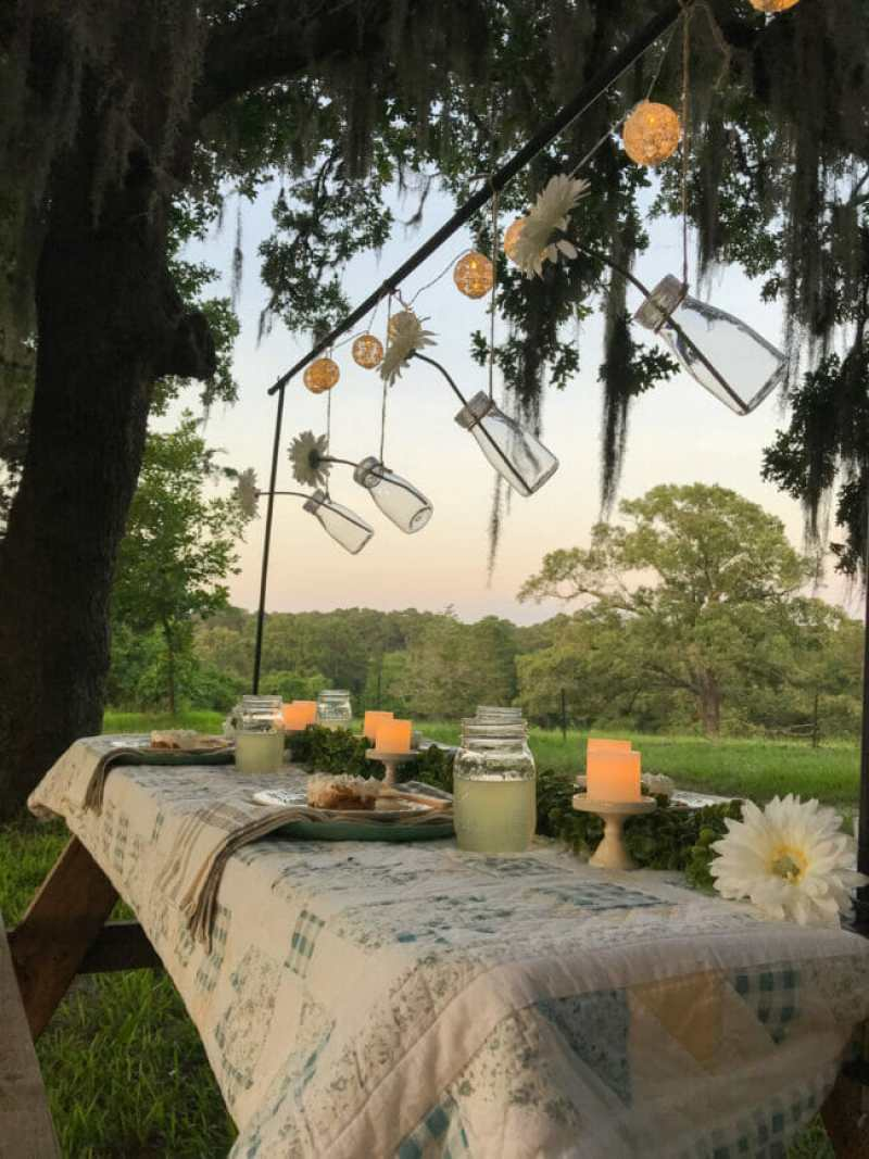 outdoor Picnic table with quilt and hanging bottles with flowers
