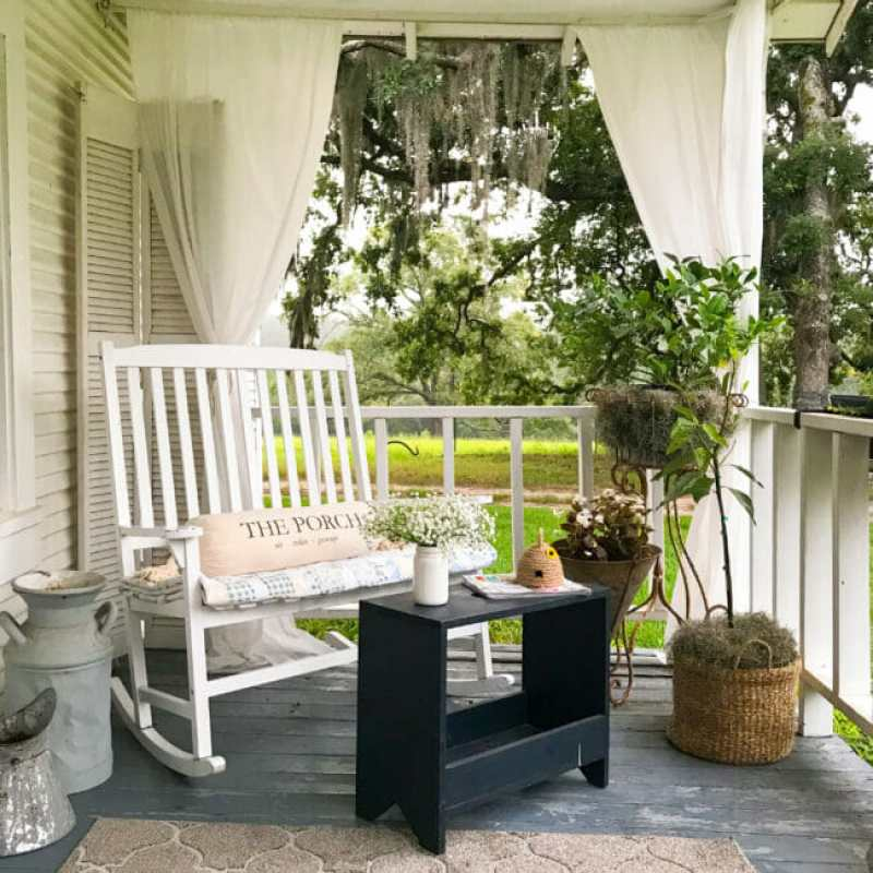 porch with plants, white rocking bench and navy stool