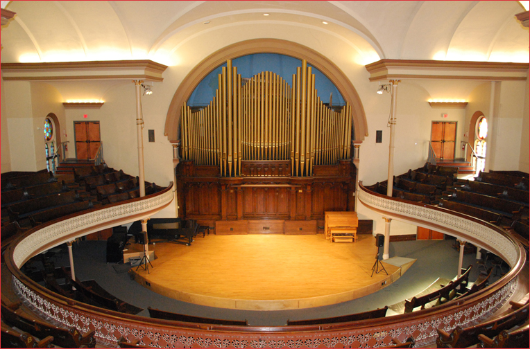Beautiful space with a rounded auditorium surrounding a stage backed with a fine looking pipe-organ.  Nice.