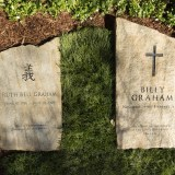 """: A slab of North Carolina stone marks the grave of Billy Graham, buried next to his wife, Ruth, at the Prayer Garden located next to the Billy Graham Library in Charlotte. The marker inscription bears the text, """"Preacher of the Gospel of the Lord Jesus Christ"""" with the Scripture reference, John 14:6. (Billy Graham's Grave Marker)"""