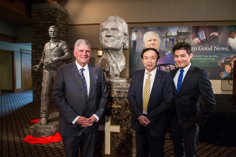 "Left to right: Franklin Graham, Chinese artist Yuan Xikun and the artist's son, Henri Yuan Xikun, posed for a photo with the bust entitled, ""Billy Graham as Messenger,"" one of two sculptures unveiled. The second is in the background to the left."