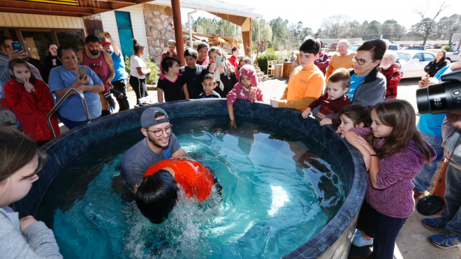 Tornado takes out Mississippi church, baptism still takes place the next day - Church members watch as student pastor Craig Blaylock, left, baptizes a church member at the First Pentecostal Church in Columbus, Miss., Sunday morning, Feb. 24, 2019. The church, in the background, was destroyed by a tornado Saturday afternoon, but church members opted to go ahead with the baptisms as planned. (AP Photo/Rogelio V. Solis)