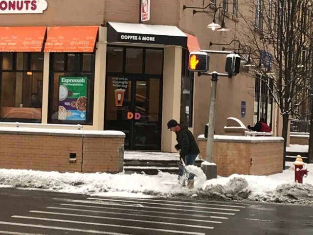 A worker clears the sidewalk at a Dunkin' Donuts in Hartford.