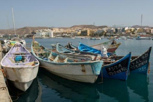 Un policier espagnol en tenue de protection inspecte plusieurs bateaux de migrants arrivés récemment à l'île de Grande Canarie (Espagne), le 14 septembre 2020 - AFP