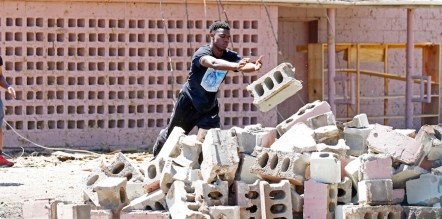 A Holmes Community College basketball player tosses a cinderblock onto a pile outside the business of Mattie Coleman, a longtime supporter of the team, as several players and their coach came to assist with helping her cleanup damage from a possible Sunday tornado that swept through Durant, Miss., on Monday, May 1, 2017. (AP Photo/Rogelio V. Solis)