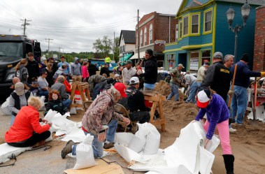 Volunteers fill sandbags in an effort to protect buildings from potential floodwater Monday, May 1, 2017, in Eureka, Mo. Torrential rain caused Missouri waterways to burst their banks over the weekend forcing hundreds of road closures and causing people to take precautions against possible flooding. (AP Photo/Jeff Roberson)