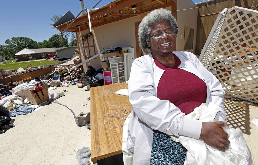 "Mattie Coleman, laughs outside what remains of her combination flower shop, thrift store and laundromat facility Monday, May 1, 2017, in Durant, Miss., as she cleans up from a possible tornado hit on Sunday morning. Coleman, a former teacher and junior high school football coach, takes a philosophical approach to what to the ""remodeling"" she has before her. (AP Photo/Rogelio V. Solis)"