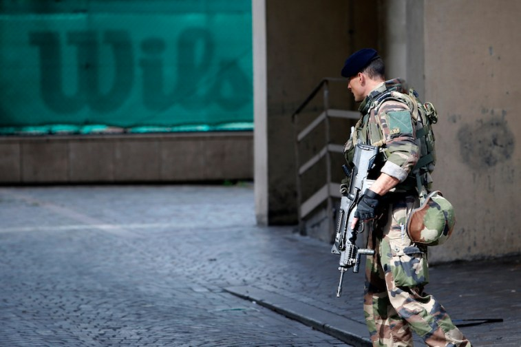 A French soldier patrols near the scene where French soldiers were hit and injured by a vehicle in the western Paris suburb of Levallois-Perret near Paris, France, on Aug. 9, 2017. French police are searching for a driver who slammed his BMW into a group of soldiers, injuring six of them in an apparent ambush before speeding away, officials said. The incident in Levallois, northwest of Paris, is the latest of several attacks targeting security forces in France. (AP Photo/Kamil Zihnioglu)