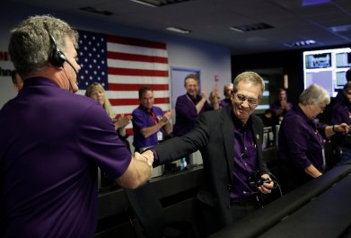 Project manager Earl Maize, center, shakes hands with Bill Heventhal in mission control at NASA's Jet Propulsion Laboratory on Sept. 15, 2017, in Pasadena, Calif., after confirmation of Cassini's demise. Cassini disintegrated in the skies above Saturn early Friday, following a remarkable journey of 20 years. (AP Photo/Jae C. Hong, Pool)
