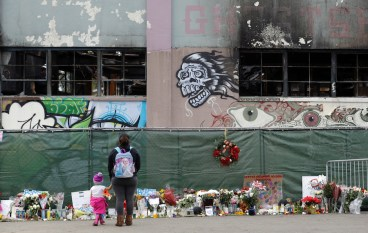 Flowers, pictures, signs and candles at the scene of a warehouse fire in Oakland, Calif., on Dec. 13, 2016. A jury has decided the fate of two men charged with involuntary manslaughter after prosecutors say they turned a San Francisco Bay Area warehouse into a cluttered maze that trapped 36 partygoers during a fast-moving fire. The verdicts for Derick Almena and Max Harris were announced Thursday after a three-month trial. (AP Photo/Marcio Jose Sanchez,File)