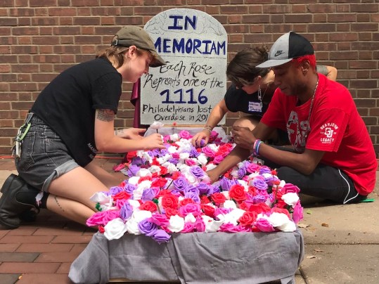 Protesters arrange roses for a monument honoring the 1,116 Philadelphia men and women who overdosed in 2018. The crowd gathered Thursday outside the Philadelphia courthouse where a federal judge heard arguments in a lawsuit to block what would be the country's first safe injection facility. Envisioned by the nonprofit Safespace, the facility would have medical staff on hand to assist should drug users overdose there on street-bought heroin or fentanyl. (Photo by ALEXANDRA JONES/Courthouse News Service)
