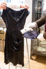 """Empolyees hold a cocktail dress, a wallet and a straw hat that belonged to Eva Braun, the wife of Adolf Hitler, prior to a Nov. 20, 2019, auction in Grasbrunn, Germany,. A Jewish group has sharply condemned an auction of Nazi memorabilia in Germany. The European Jewish Association condemned the auction Wednesday at Hermann Historica in Munich, saying that """"it's wrong to make money off these blood-soaked items, especially in Germany of all places."""" (Matthias Balk/dpa via AP)"""