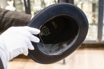 A man holds a hat with the initials of Adolf Hitler prior to a Nov. 20, 2019, auction in Grasbrunn, Germany. (Matthias Balk/dpa via AP)