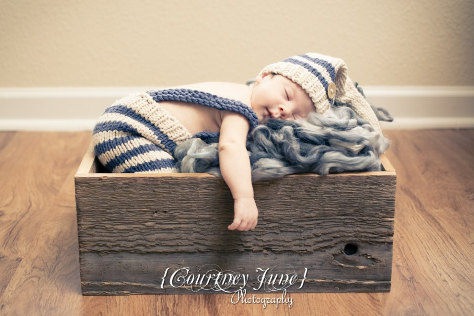 newborn photographer photographing a newborn in a wooden crate with a knit jumper