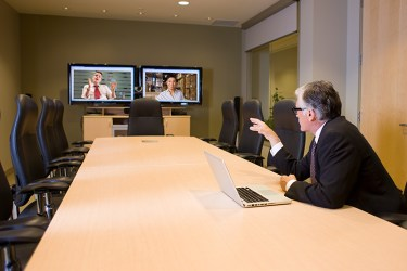 man at conference table having a video meeting