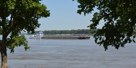 A smaller barge going down the Mississippi river