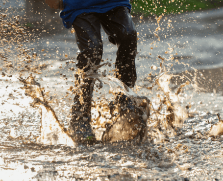 kid jumping in mud