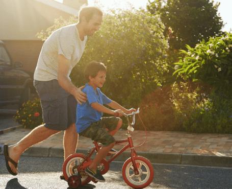 dad teaching son to ride a bike