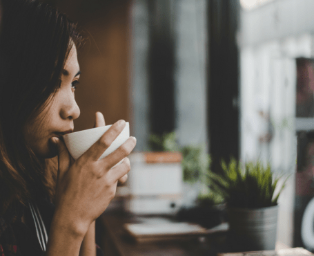pensive woman drinking cup of coffee