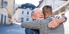 dad hugging adult son on street