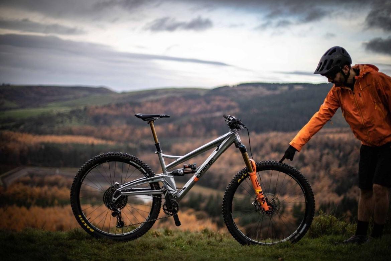 Fahrrad fahren im Winter: Was solltest Du beachten?: Mann der auf seinen Fahrradreifen zeigt.