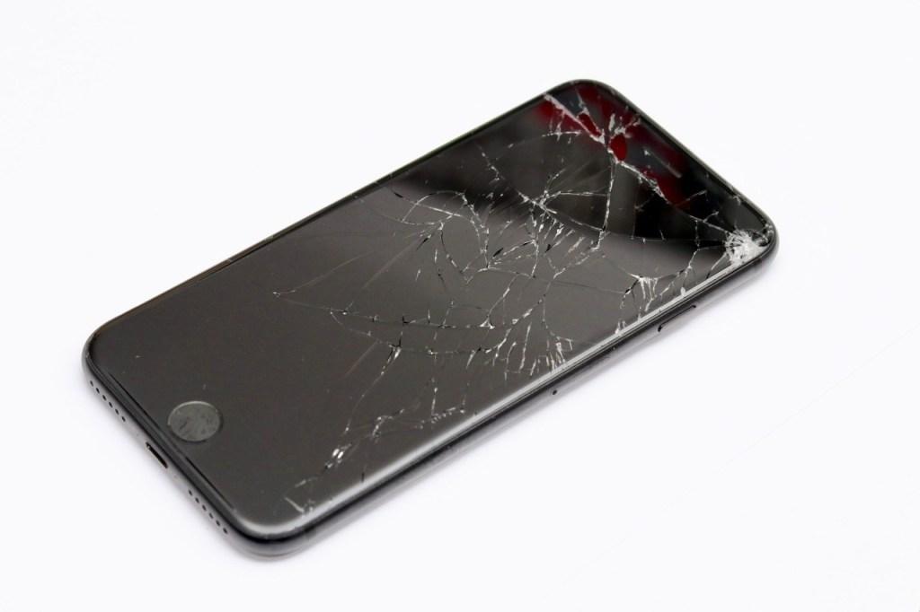 Displayreparatur: iPhone mit zersplittertem Display auf weißem Hintergrund