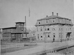 View of the Corey Needle Works on Concord Street. Looking south east Maple Street is seen in the foreground and runs north and south. A man stands on the corner in front of a three story second empire house with mansard roof. [That house is William Corey's home, and it is still standing].
