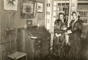 Old postcard showing two women posing in a room of antiques in the Goyette Museum.