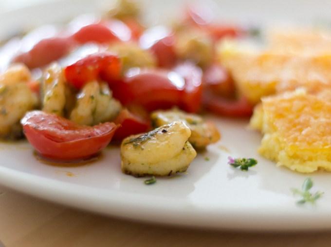 Resteverwertung auf die Elegante Art. Polenta schmeckt nämlich nicht nur frisch als warmer Brei aus dem Topf ganz toll, sondern auch gebacken oder gebraten. Mit Parmesan bestreut sogar noch ein bisschen feiner und Herzhafter! MMMHHHH In der Kombination mit frischen und fruchtigen Tomaten und Garnelen sind sie die perfekte Beilage