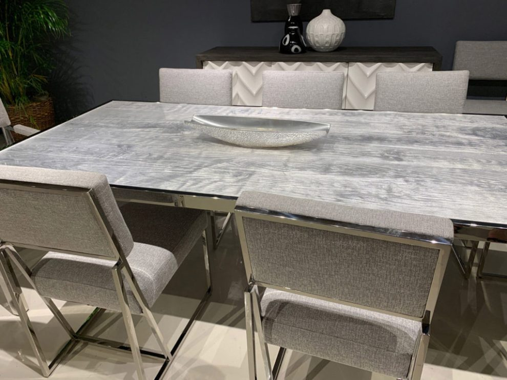 contemporary wood grain table and grey dining chairs with metallic frame Spring 2019 Design Trends - High Point Market