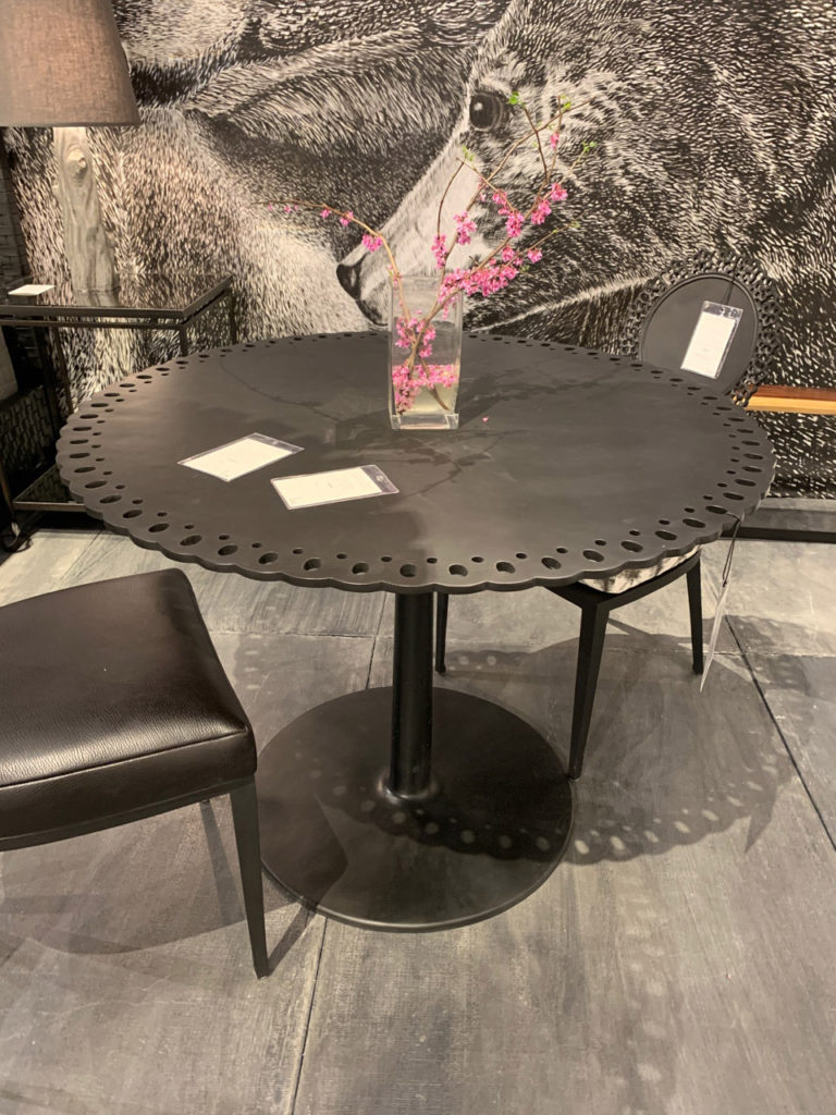 Gothic table with grey wood grain floor and dark chairs Spring 2019 Design Trends - High Point Market