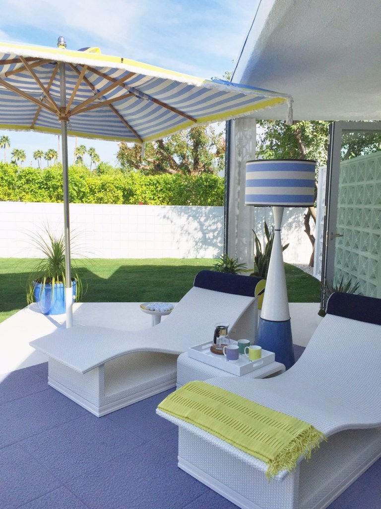 Chaise lounges with umbrella and cordless floor lamp in Palm Springs.