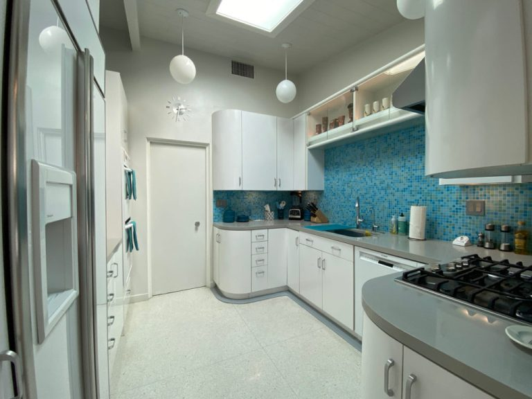 White mid century modern kitchen with turquoise tile backsplash and grey countertop.